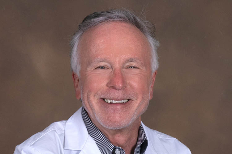 Dr. Jerman smiling in a white lab coat on a brown background