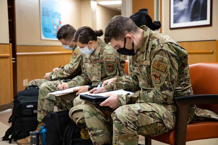 Uniformed air force personnel sit and fill out paperwork in a hospital lobby