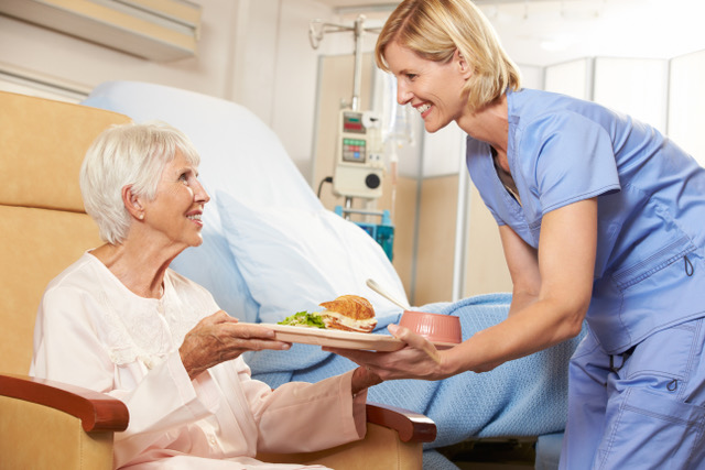 nurse serving meal to patient